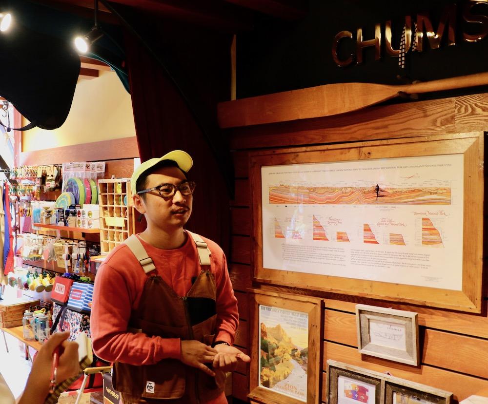 インタビューさせていただいたチャムス表参道店中野店長。その後ろにはユタ州ザイオン国立公園の地質図が貼られている。